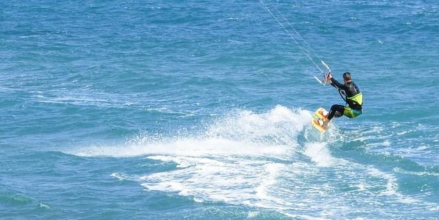 Deportista realizando trucos de kitesurf en el mar